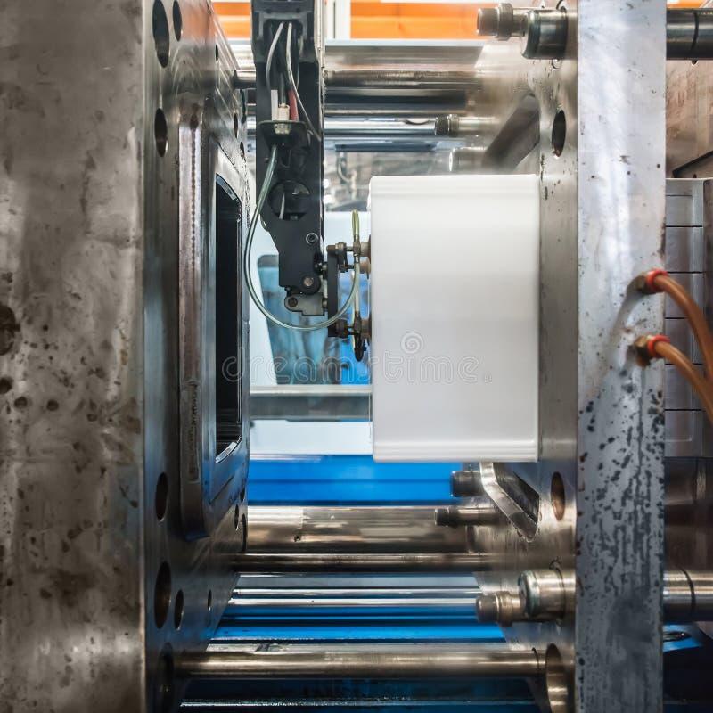 Plast- injektionstöpningsmaskin som arbetar i fabrik arkivbilder