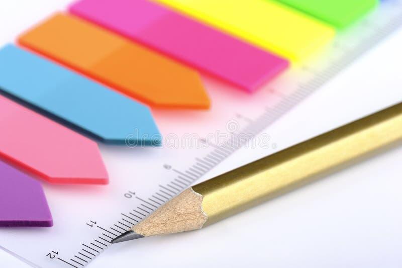 Plast- klistermärkear, bokmärker och blyertspenna royaltyfria foton