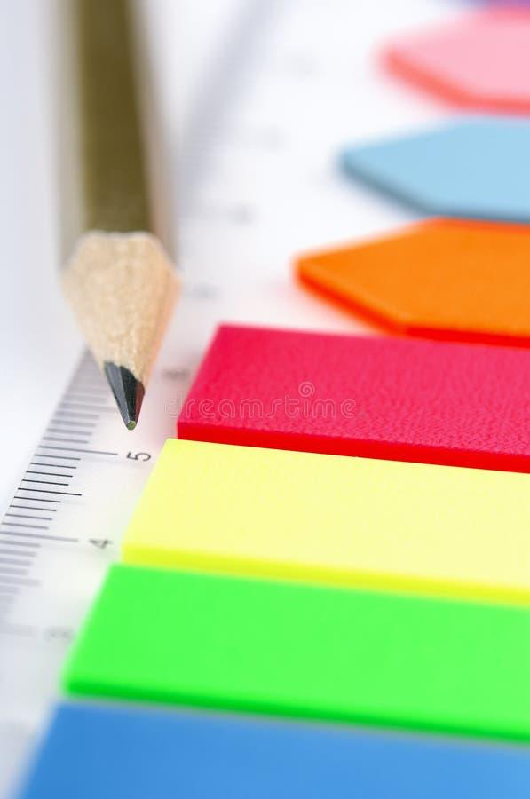 Plast- klistermärkear och blyertspennacloseup arkivfoton