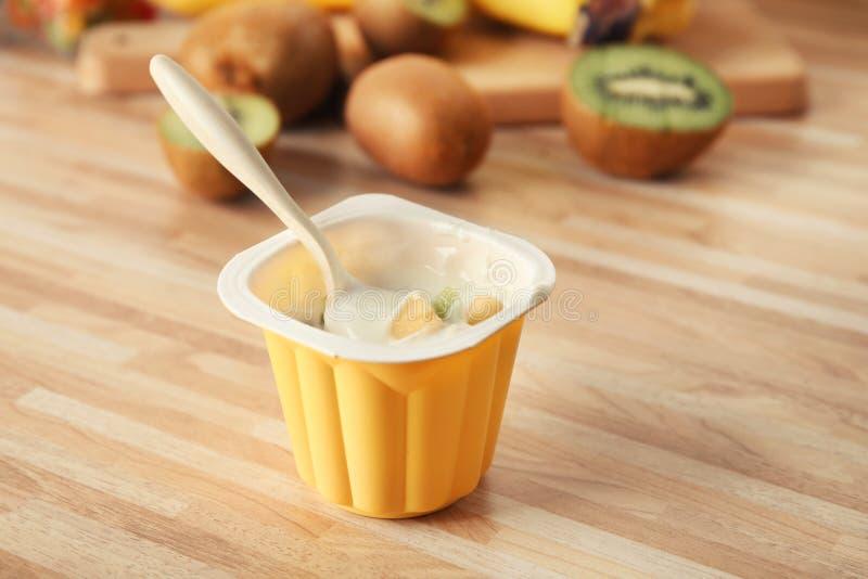 Plast- kopp av smaskig yoghurt med tropiska frukter arkivbilder