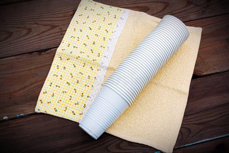 Plast-koppar på träbakgrund arkivfoton