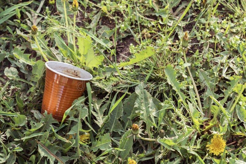 Plast- koppavfalls och avskräde som ligger på grönt gräs Problemet av miljö- förorening royaltyfri foto
