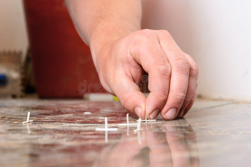 Plast- kors för att lägga tegelplattor på golvet sprids över tegelplattan royaltyfria foton