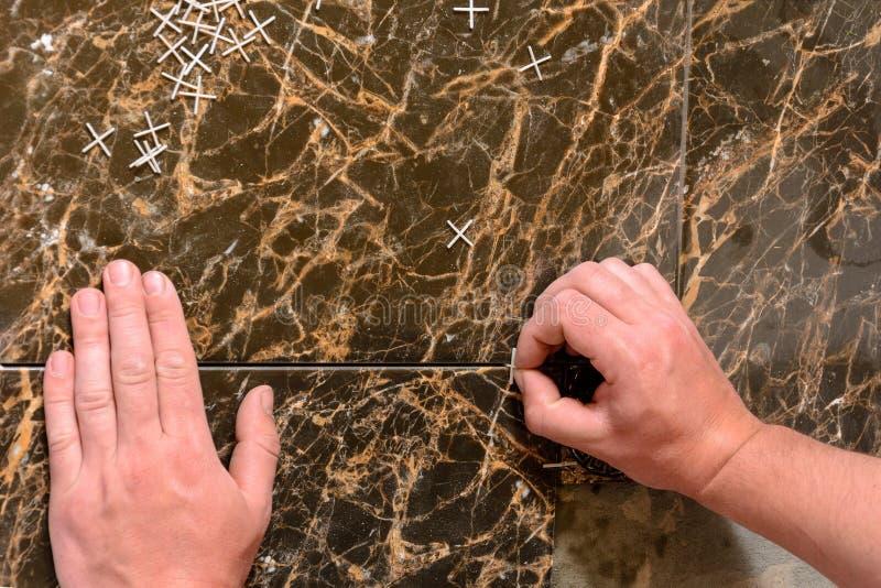 Plast- kors för att lägga tegelplattor på golvet sprids över tegelplattan arkivfoto
