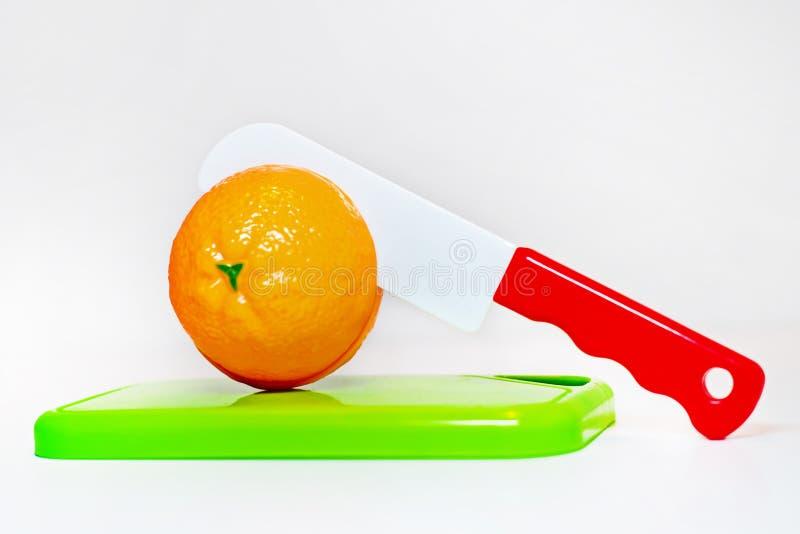 Plast- leksakapelsin på ett skärbrädasnitt i halva med en plast- kniv royaltyfri fotografi
