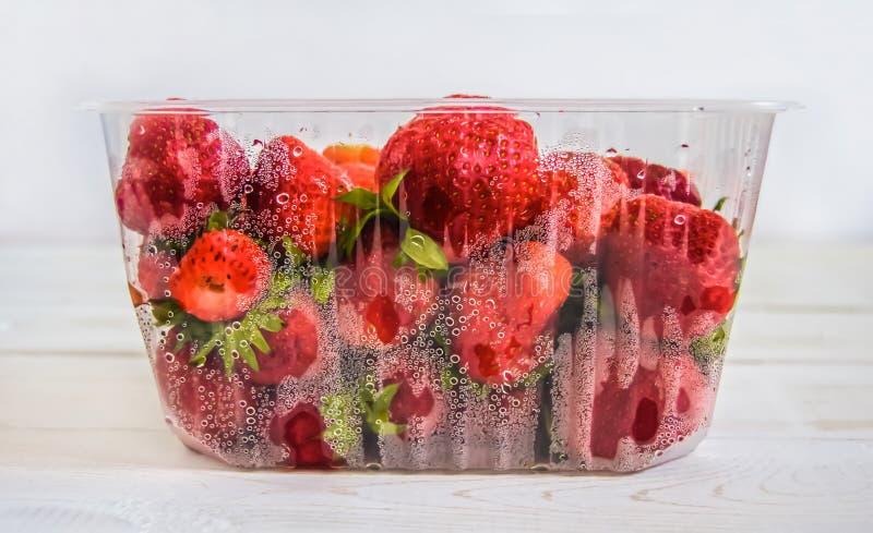Plast- magasin med röda jordgubbar på en vit träbakgrundssidosikt arkivfoton