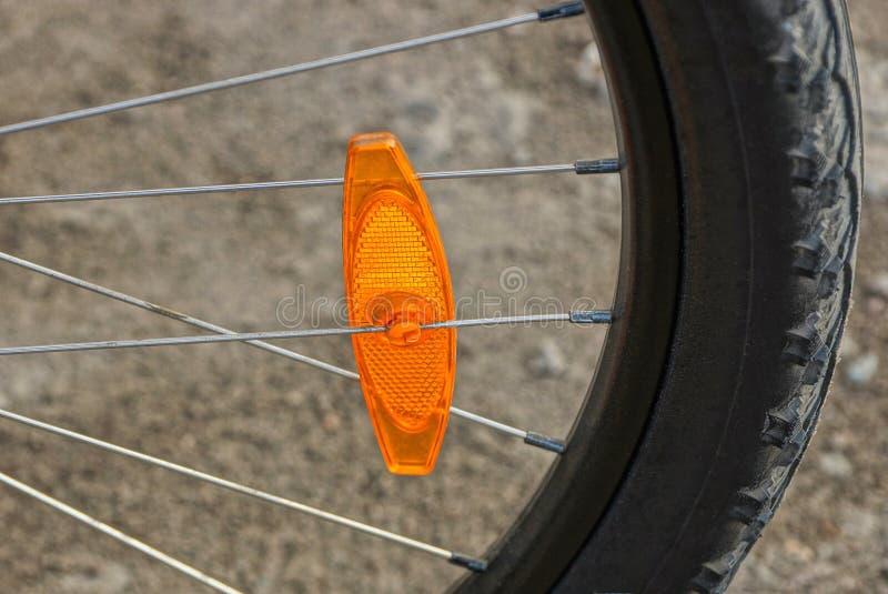Plast- orange reflektor på den gråa metalleker av det svarta hjulet på en cykel royaltyfri fotografi