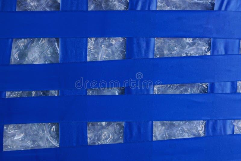 Plast- randig textur av det blåa elektriska bandet på vit cellofan arkivfoton