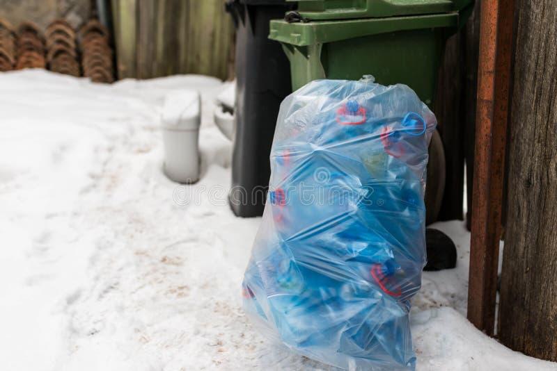 Plast- säck som fylls med blåa plast- mineralvattenflaskor arkivfoton