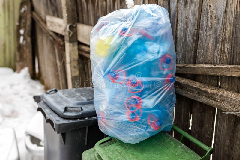 Plast- säck som fylls med blåa plast- mineralvattenflaskor arkivfoto