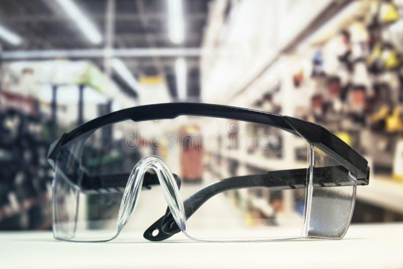 Plast- säkerhetsskyddsglasögon, på tabellen och bakgrunden av maskinvarulagret med hjälpmedel arkivbilder
