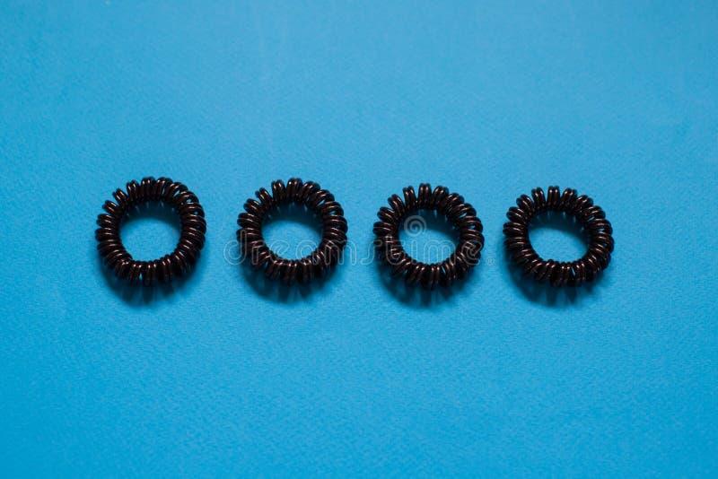 Plast- spirala scrunchies för hår på blå bakgrund, kvinnligt begrepp för skönhetflicka arkivfoton