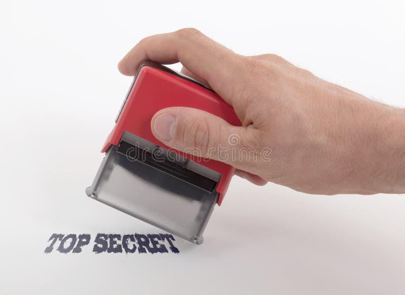 Plast- stämpel i handen som isoleras arkivbild