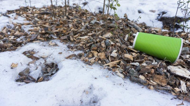 Plast- tar bort kaffekoppen som avfall på snö royaltyfri foto
