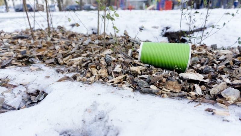 Plast- tar bort kaffekoppen som avfall på snö royaltyfria bilder