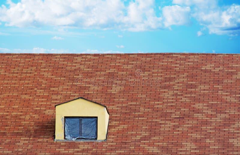 Plast- torkduk på en takfönster i ett tegelplattatak arkivbilder