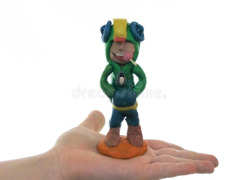 Plastellinapojke med godisen i hans mun, på handen av ett barn royaltyfri foto