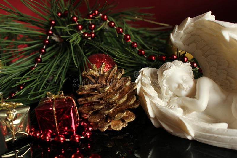Plaster angel - Christmas background. Plaster angel with small presents, Christmas decoration and golden cone royalty free stock image