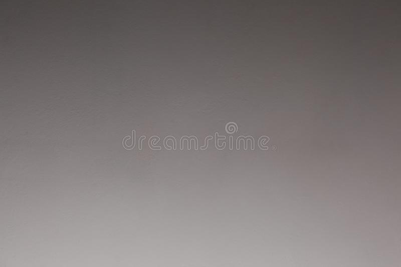 Close up on a plaster wall fading from light grey to dark gray with copy space for your text. Plaster wall fading from light grey to dark gray royalty free stock images