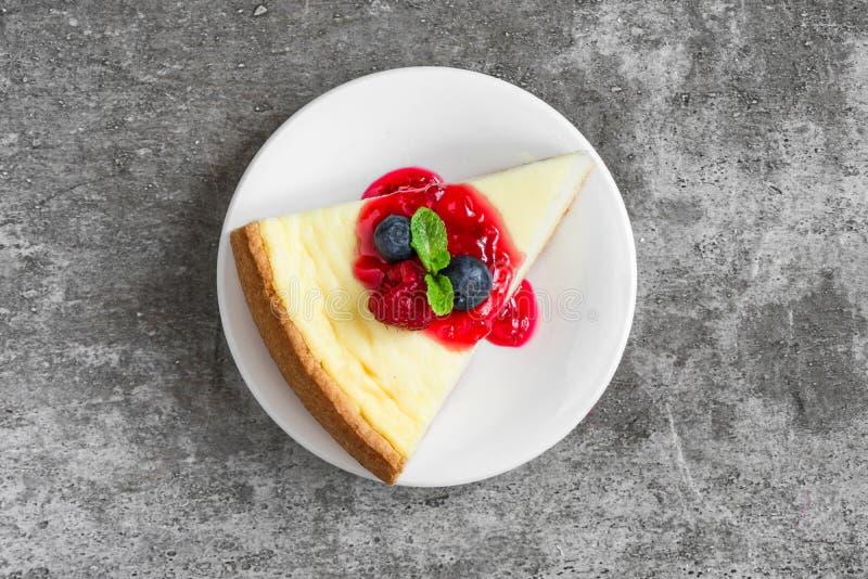 Plasterek cheesecake z świeżymi malinkami, czarnymi jagodami, dżemem i mennicą na betonowym tle, Odgórny widok zdjęcie stock