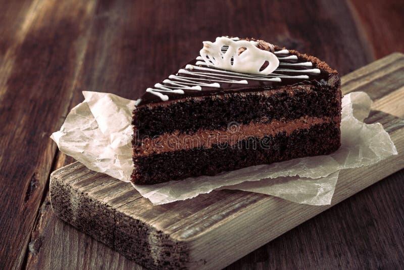 Plasterek domowej roboty czekoladowy tort na drewnianej tnącej desce, wieśniaka styl zdjęcie royalty free