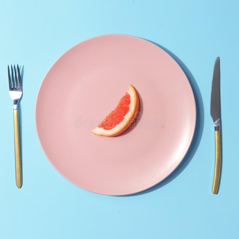 Plasterek grapefruitowy na różowym talerzu Minimalistic poj?cie Odg?rny widok obraz stock