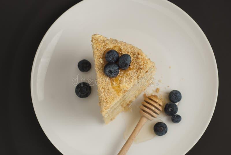 Plasterek płatowatego domowej roboty miodowego torta selekcyjnej ostrości bluebery round talerza czerni białego tła odgórny widok zdjęcia stock