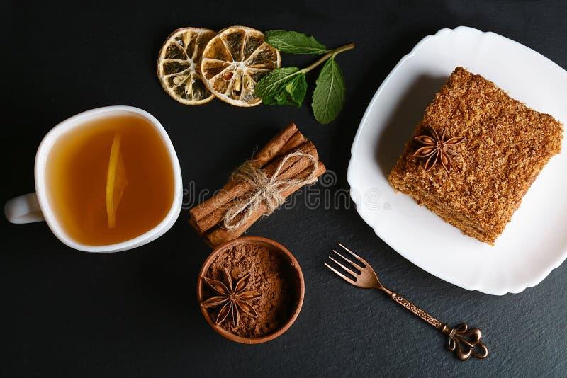 Plasterek płatowaty miodowy tort dekorujący z anyż gwiazdą, deserowy rozwidlenie, mennica, wysuszone cytryny, kije cynamon, surow obrazy stock