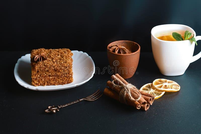 Plasterek płatowaty miodowy tort dekorujący z anyż gwiazdą, deserowy rozwidlenie, mennica, wysuszone cytryny, kije cynamon, surow fotografia stock