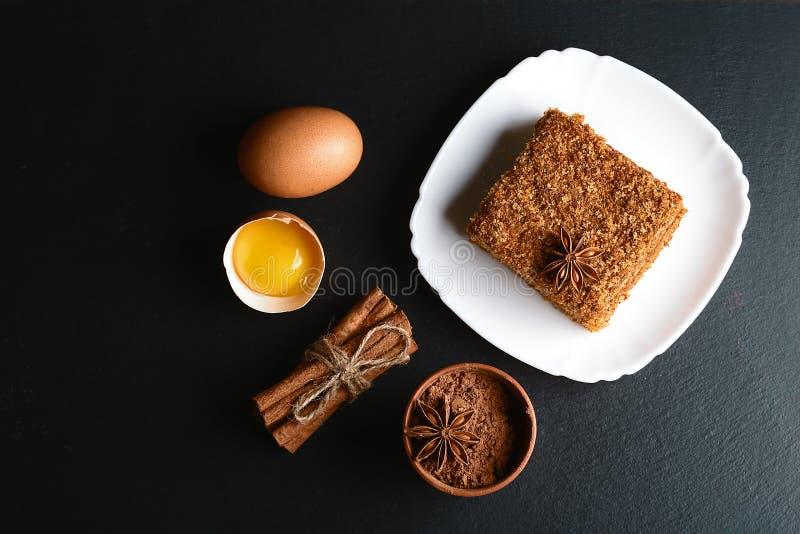 Plasterek płatowaty miodowy tort Medovik dekorujący z anyż gwiazdą na bielu talerzu, kije cynamon, surowi jajka, kakaowy proszek, zdjęcia royalty free