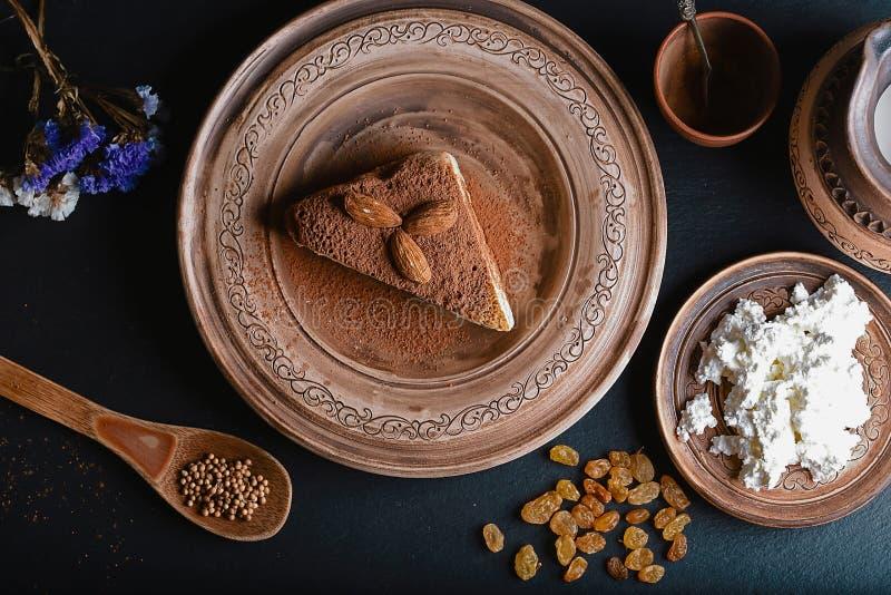 Plasterek polany miodowy tort z serową śmietanką na glinianym rocznika talerzu, dekorujący z kakao i migdałami, drewniana łyżka z zdjęcie stock