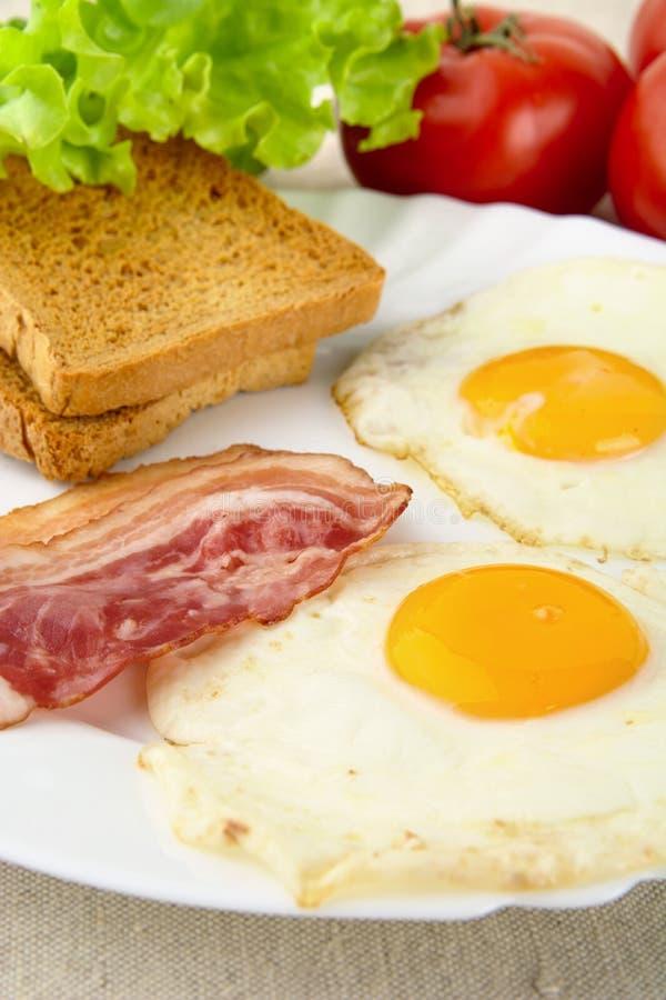 Plasterek smażący bekon, dwa jajka na talerzu z grzankami dla śniadania zdjęcia royalty free
