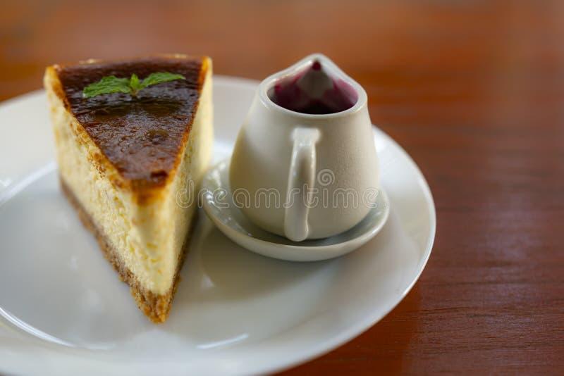 Plasterek wyśmienity świeży tortowy kulebiak z słojem czarna jagoda na białym talerzu z drewnianym stołem obraz royalty free