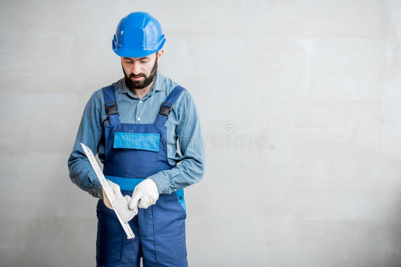 Plasterer with spatula indoors. Plasterer in blue working uniform cleaning spatula standing on the grey wall background stock image