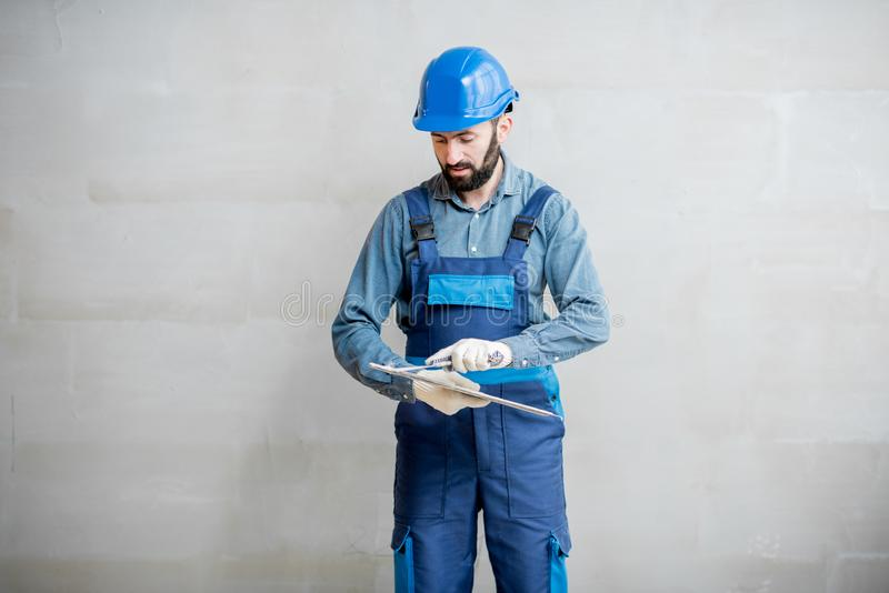 Plasterer with spatula indoors. Plasterer in blue working uniform cleaning spatula standing on the grey wall background stock photos