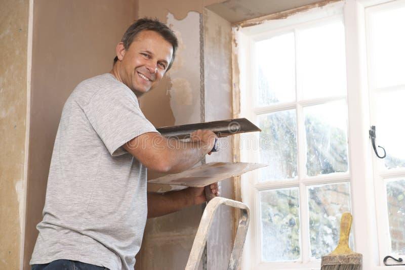 Plasterer che lavora alla parete interna fotografia stock libera da diritti