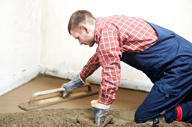 Plasterer concrete worker at floor work. Plasterer at indoor concrete cement floor topping with float royalty free stock image