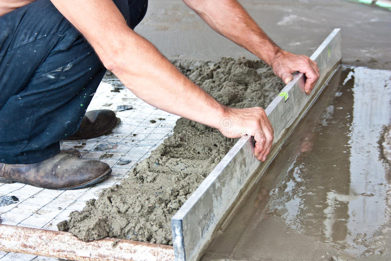 Plasterer concrete worker at floor work. Of construction site royalty free stock image