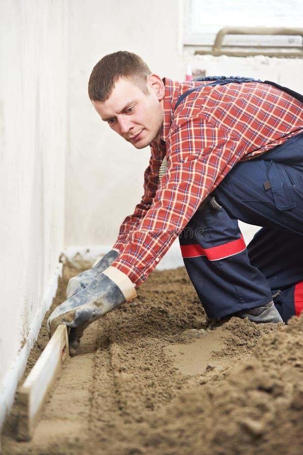 Plasterer concrete worker at floor work royalty free stock images