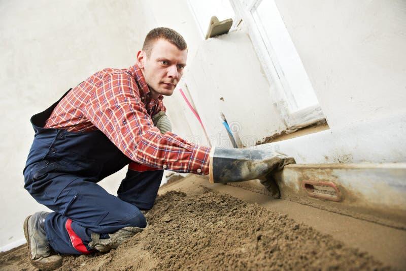 Plasterer concrete worker at floor work stock photo