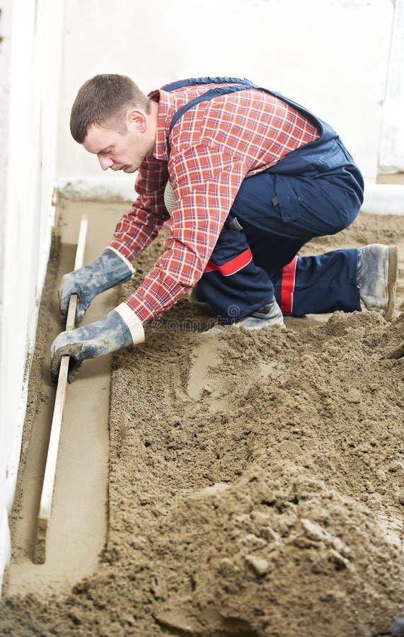 Plasterer concrete worker at floor work stock image