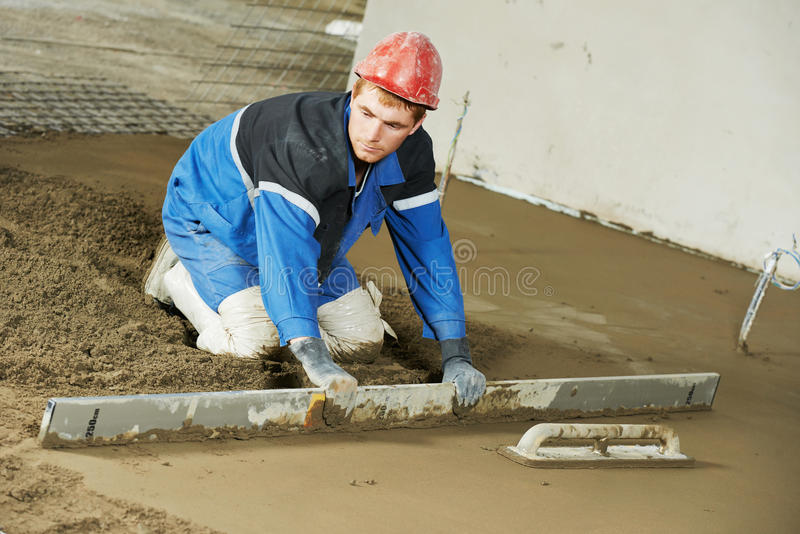 Plasterer concrete worker at floor work stock photos