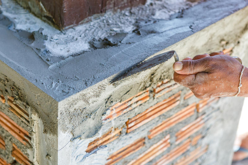 Plasterer concrete worker at wall of house construction stock image