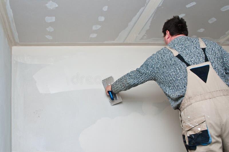 Plasterer or dry waller at work stock image