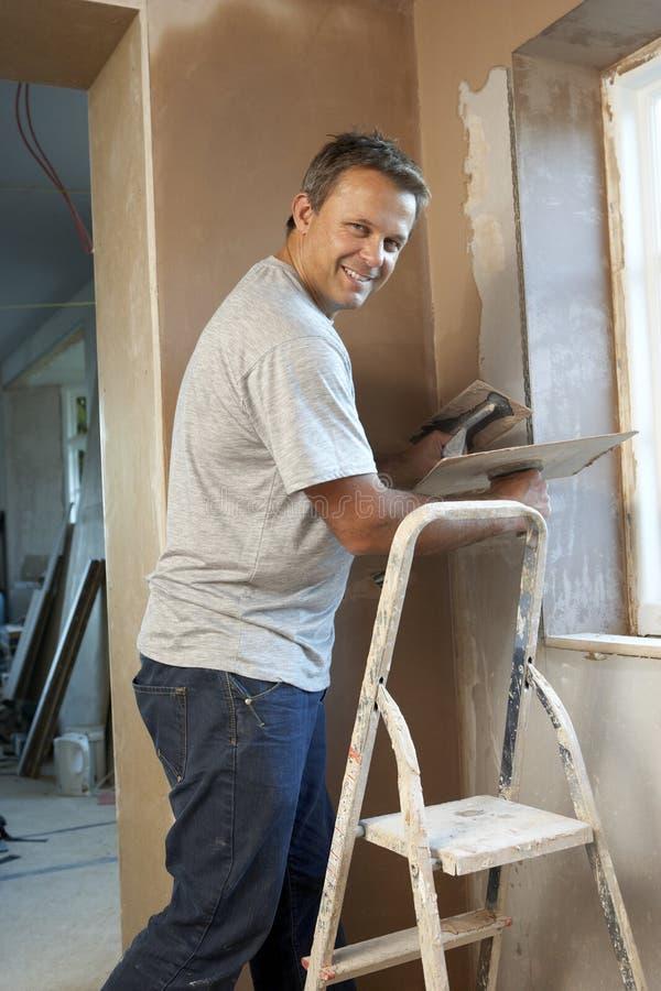 Plasterer que trabalha na parede interior fotos de stock royalty free