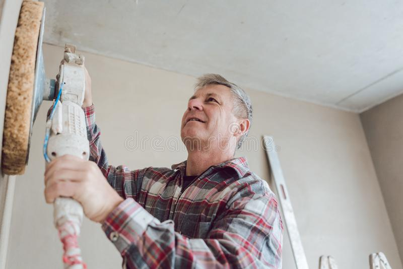 Plasterer smoothing interior wall with machine stock photos