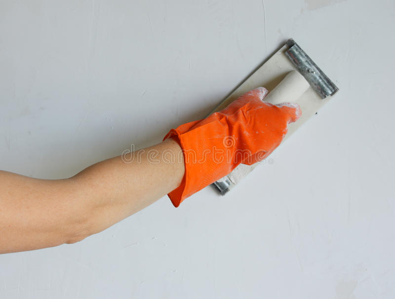 Plasterer smoothing out wall with trowel royalty free stock photos