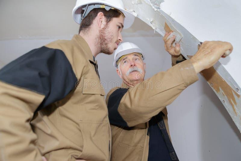 Plasterer teaching apprentice how to scrape wallpaper stock photography