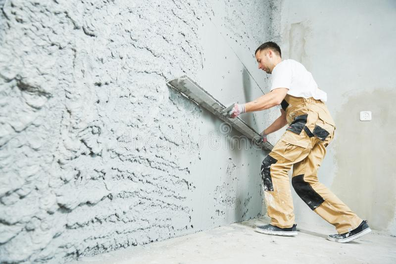 Plasterer using screeder smoothing putty plaster mortar on wall. Plasterer using screeder smoothing thin-layer putty plaster mortar finishing on brick wall stock image