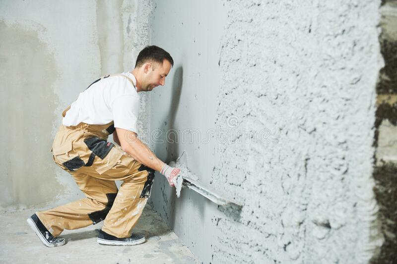 Plasterer using screeder smoothing putty plaster mortar on wall. Plasterer using screeder smoothing thin-layer putty plaster mortar finishing on brick wall royalty free stock image